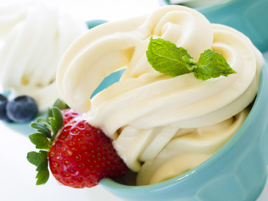Cup of soft-serve frozen yogurt on white background.